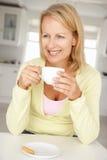 Mitt- ålderkvinna med hemmastatt kaffe Arkivfoton