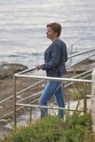 Mitt åldrades den caucasian kvinnan som hänsynsfullt ser in i havet Arkivfoto