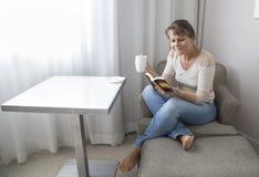 Mitt åldrades kvinnan som läser en bok och dricker kaffe Arkivfoton