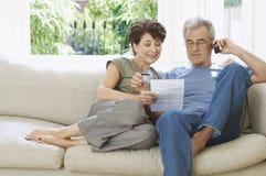 Mitt åldrades par som betalar Bill By Phone Royaltyfri Bild