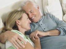 Mitt åldrades par som omfamnar i säng Royaltyfri Foto
