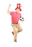 Mitt åldrades sportfanen med hatten som rymmer en boll och gör en gest happ Fotografering för Bildbyråer