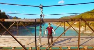 Mitt--luft flyg över turisten för ung man som blir över en upphängningbro lager videofilmer
