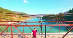 Mitt--luft flyg över turisten för ung man som blir över en upphängningbro arkivfilmer