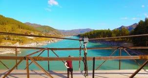 Mitt--luft flyg över turisten för ung man som blir på en bro och hålla ögonen på för upphängning arkivfilmer