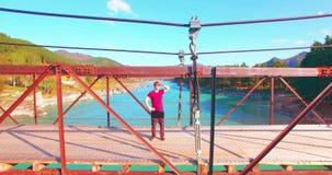 Mitt--luft flyg över turisten för ung man som blir på en bro och hålla ögonen på för upphängning stock video