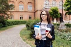 Mitt studentliv Lycklig le studentflicka med ryggsäcken på universitetbakgrund Kvinna med arbetsböcker och att ta bort kaffehavi arkivfoto