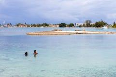Mitt två åldrades Micronesian kvinnor i stängande tyckande om simning i den steniga blåa turkoslagun, den Majuro staden i bakgrun arkivbild