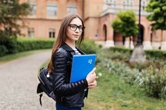 Mitt universitetliv Lycklig gullig student för ung kvinna med ryggsäcken som rymmer böcker och går på collage arkivfoto