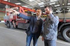 Mitt- vuxen affärsman med arbetsledaren som har diskussion i metallbransch arkivbilder