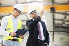Mitt- vuxen affärsman med arbetsledaren som har diskussion i metallbransch royaltyfri bild