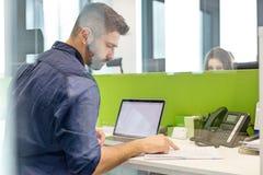 Mitt- vuxen affärsman med bärbar datorläseboken på skrivbordet i regeringsställning Royaltyfria Bilder