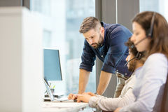 Mitt- vuxen affärsman som använder bärbara datorn med coworkers som i regeringsställning bär hörlurar med mikrofon Royaltyfri Bild