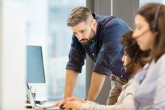 Mitt- vuxen affärsman som använder bärbara datorn med kollegor som i regeringsställning bär hörlurar med mikrofon Royaltyfri Bild