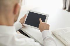 Mitt- vuxen affärsman som använder den digitala datoren på tabellen i inrikesdepartementet Fotografering för Bildbyråer
