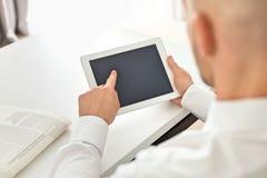 Mitt- vuxen affärsman som använder den digitala datoren på tabellen i inrikesdepartementet Arkivbilder