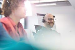Mitt- vuxen affärsman som använder hörlurar med mikrofon med manliga kollegor i förgrund på kontoret arkivfoto