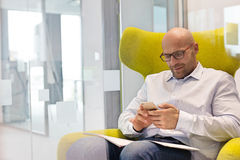 Mitt- vuxen affärsman som använder mobiltelefonen, medan sitta på stol på kontoret arkivfoton