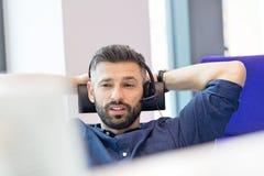 Mitt- vuxen affärsman som i regeringsställning använder hörlurar med mikrofon arkivbild