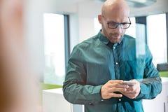 Mitt- vuxen affärsman som i regeringsställning använder mobiltelefonen Fotografering för Bildbyråer