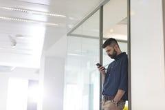Mitt- vuxen affärsman som i regeringsställning använder mobiltelefonen Arkivfoto