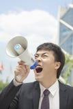 Mitt- vuxen affärsman som skriker in i en megafon, utomhus, Peking, Kina Fotografering för Bildbyråer