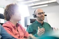 Mitt- vuxen affärsman som talar på hörlurar med mikrofon med manliga kollegor i förgrund på kontoret arkivbilder