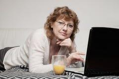Mitt- vuxen kvinna med bärbara datorn Arkivfoto