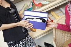 Mitt- vuxen kvinna som ger skodon till den mogna kunden i skolager Arkivbilder