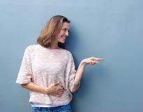 Mitt- vuxen kvinna som ler och pekar fingret för att kopiera utrymme Royaltyfri Fotografi