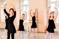 Mitt- vuxen kvinnlig balettlärare som framme visar flyttningar av en grupp av tonårs- flickor royaltyfria bilder