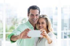 Mitt- vuxna par som hemma tar selfie arkivbilder