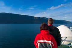 Mitt- vuxna par som stirrar på den härliga Naeroyfjorden Arkivbild