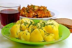 Mittagessen gebratene Fische, gekochte Kartoffeln und Rotwein Stockfotografie