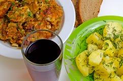 Mittagessen gebratene Fische, gekochte Kartoffeln und Rotwein Stockbild