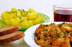 Mittagessen gebratene Fische, gekochte Kartoffeln und Rotwein Lizenzfreie Stockfotos