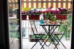 Mittagessen im Freien in einem Balkon voll von Surfinias Stockfotografie