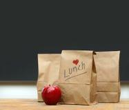 Mittagessenbeutel mit Apfel auf Schuleschreibtisch Stockfotografie