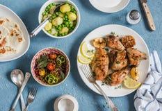 Mittagessentabelle Gebackenes Huhn der Zitrone Thymian, gekochte Kartoffeln mit grünen Erbsen, Salat mit Linsen und Tomaten, Flat lizenzfreies stockbild