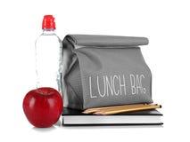 Mittagessentasche, Flasche Wasser, Apfel und Briefpapier Lizenzfreies Stockfoto