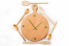Mittagessenzeit. Mahlzeiten. Uhren werden vom Grün hergestellt. Stockbilder