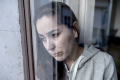 Mitte alterte das lateinische traurige und deprimierte Schauen der Frau durch den Fenster Refection im Krisenkonzept lizenzfreie stockfotos