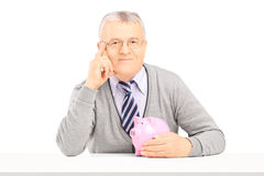 Mitte alterte den Mann, der auf einer Tabelle mit Sparschwein aufwirft Stockfoto
