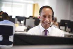 Mitte alterte den Mann, der am Computer mit Kopfhörer im Büro arbeitet lizenzfreies stockfoto