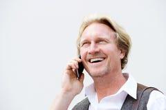 Mitte alterte den Mann, der am Handy gegen weiße Wand spricht Lizenzfreies Stockfoto