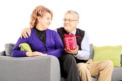 Mitte alterte den Mann, der seiner Frau ein Geschenk gibt Stockfoto