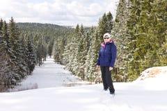 Mitte alterte den weiblichen Reisenden, der auf einen Hügel gegen den Winterwaldhintergrund steht Stockbild