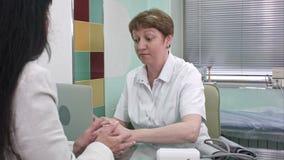 Mitte alterte die Ärztin, die vor Laptop sitzt und ihren Patienten konsultiert stock video footage