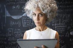 Mitte alterte die akademische Frau, welche die Tablette verwendet, die zur Kamera schaut stockbilder