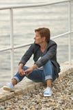Mitte alterte die kaukasische Frau, die auf dem Seestrand sitzt Lizenzfreie Stockfotos